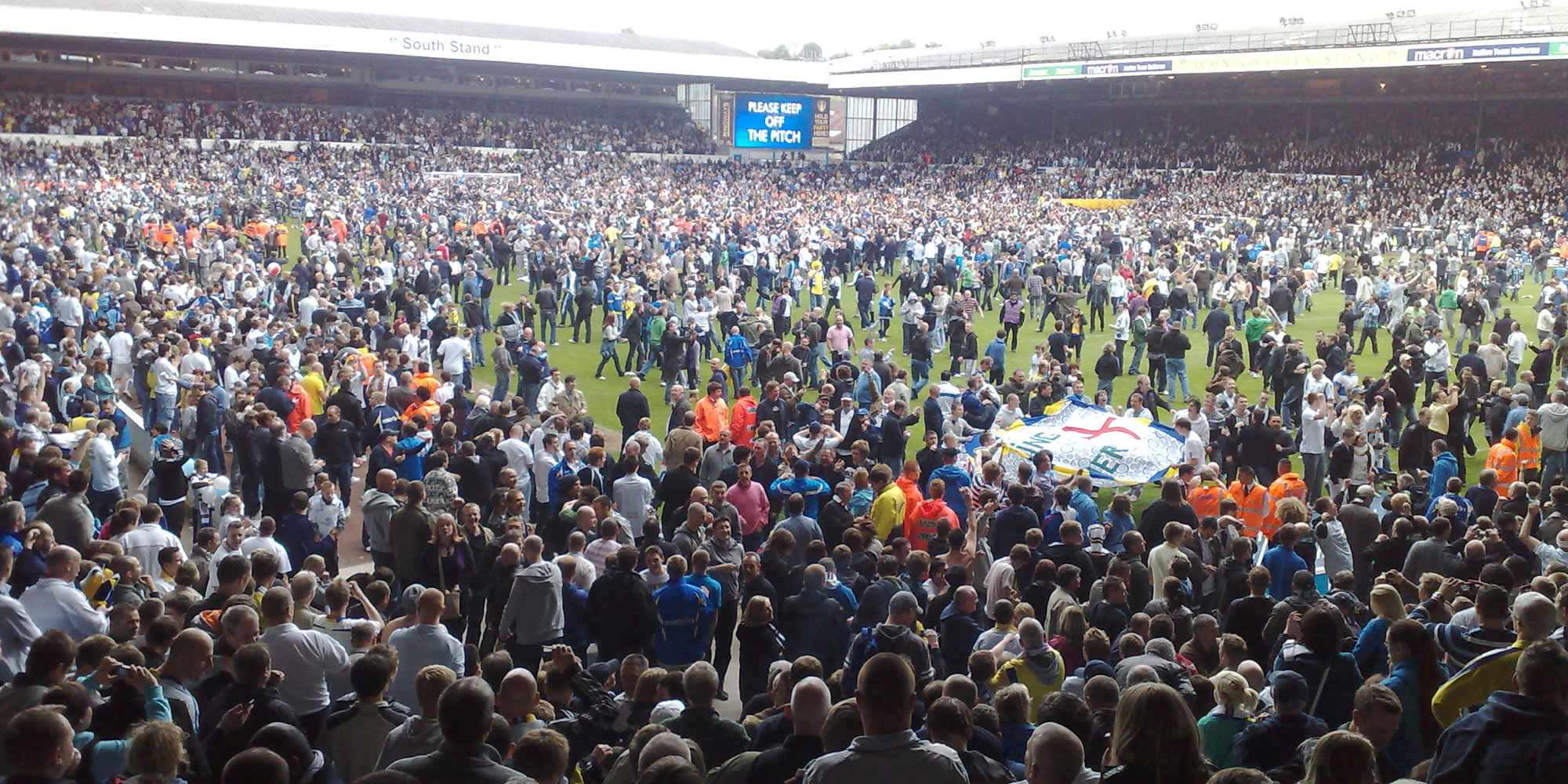 Photo: fans on the pitch at Elland Road.